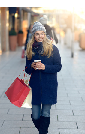 Gorgeous young woman out Christmas shopping in a knitted winter cap smiling happily as she glances behind her while walking in an urban street