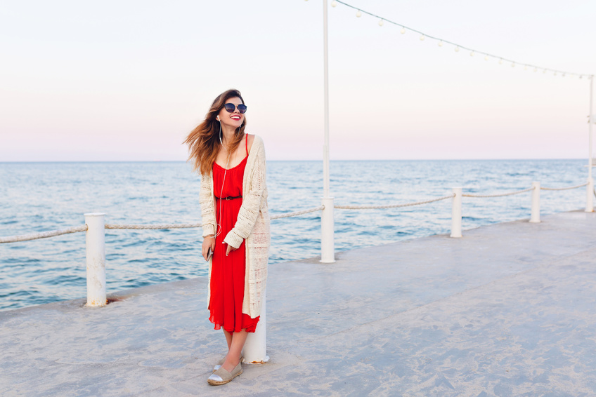 Beautiful girl in red dress and white jacket stands on a pier, smiles, and listens to music on earphones on a smartphone. Girl has ombre hair. She wears light brown espadrilles and dark sunglasses.