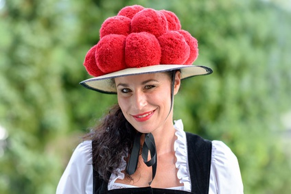Attractive young woman wearing a traditional Black Forest Bollenhut with its 14 pompoms as she smiles at the camera outdoors against greenery